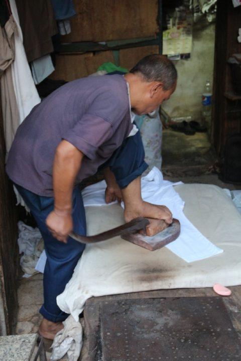 عم رفعت علي المكوجي يستخدم مكواة الرجل في كي الملابس - تصوير: صديق البخشونجي