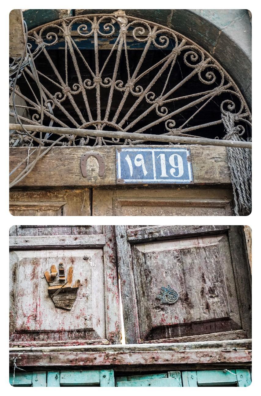 الصورة العلوية: حدوة حصان معلقة على باب أحد البيوت بشارع القادرية. الصورة السفلية: كف (خمسة وخميسة) بشكلين مختلفين على نافذة أحد البيوت بمنطقة عرب اليسار.