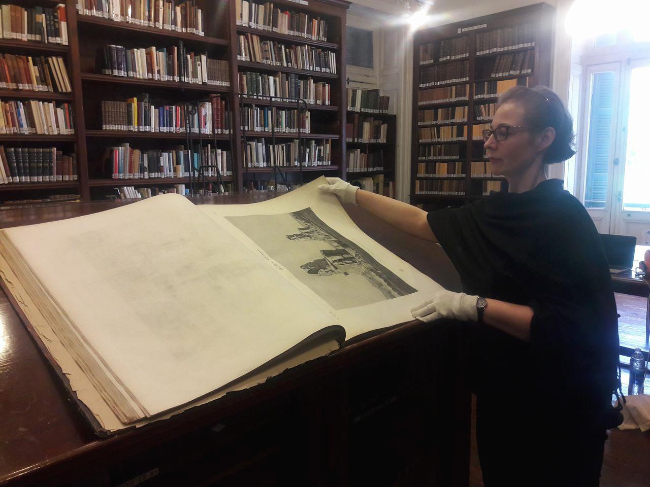 تقلب آنييس بقفازها الأبيض بكل إجلال صفحات كتاب وصف مصر